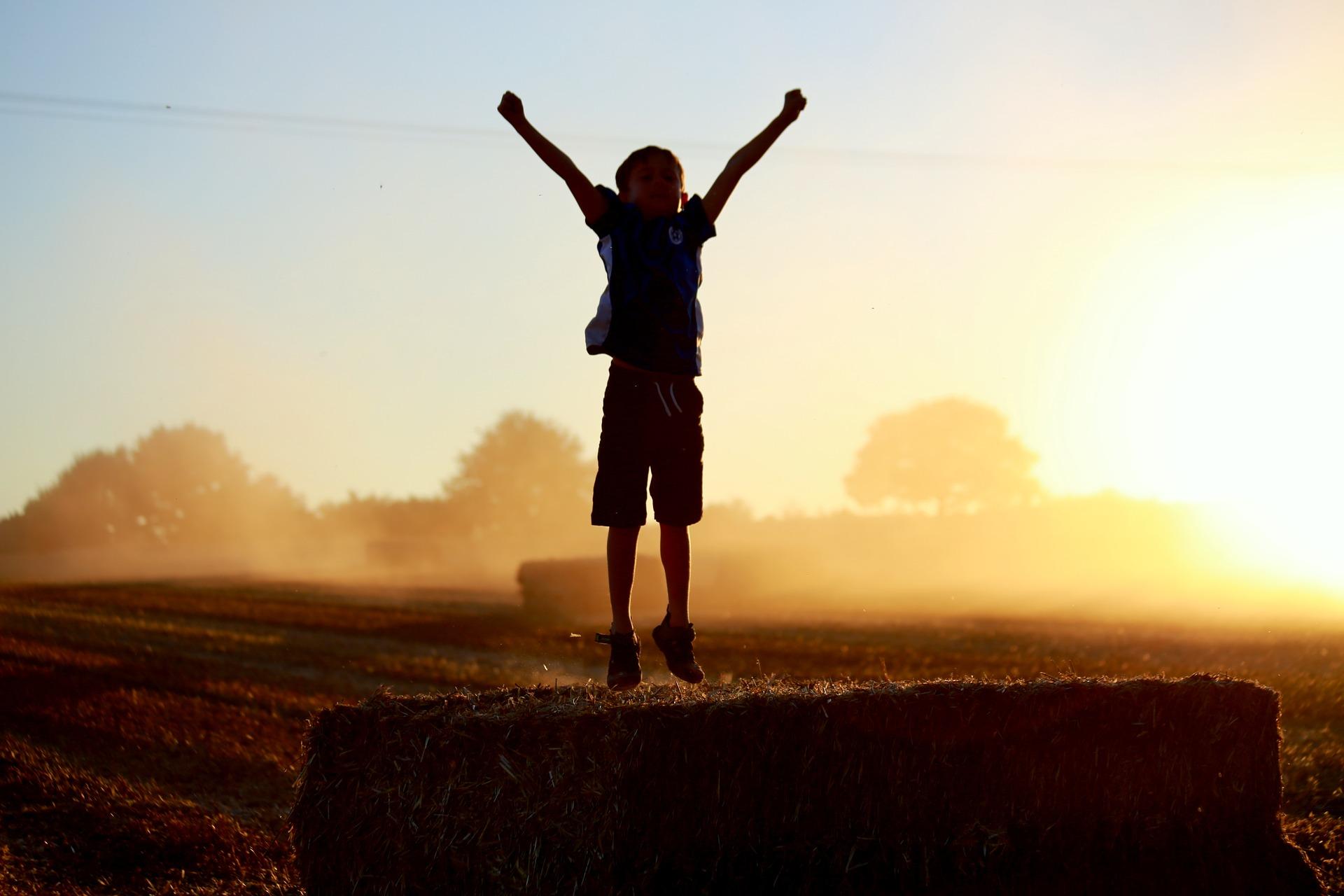 Enfant heureux sautant sur paille